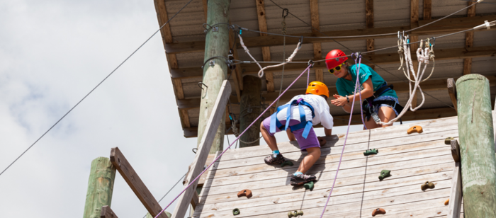 Child on rock climbing course at special needs camp in Rockport, Tx.